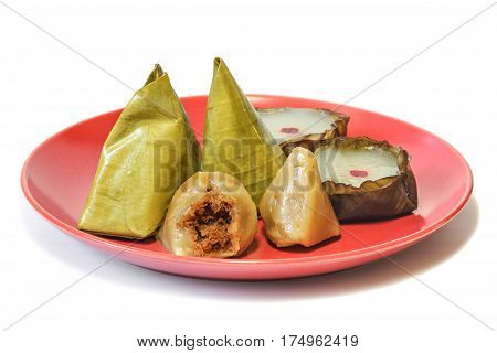 Stuffed Dough Pyramid Dessert (Ka-Nhom-Tian) wrapped with banana leaf in pyramid shape and Nian gao (Chinese new year's rice cake) for celebrate Chinese new year festival on white background, dessert.