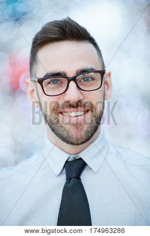 Head and shoulders portrait of young confident bearded businessman wearing glasses and white shirt with tie smiling cheerfully against blurred office background