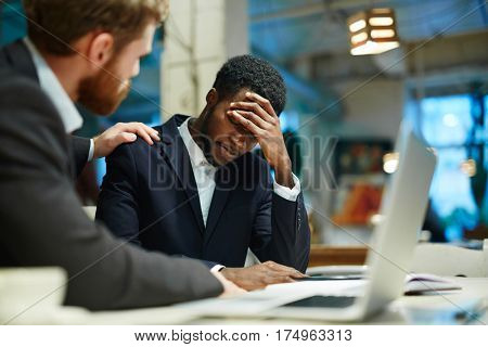 Overworked businessman showing tiredness, his colleague reassuring him