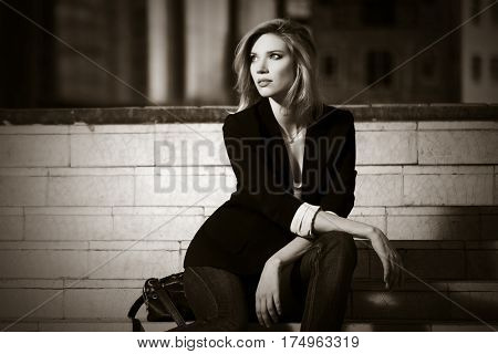 Young business woman sitting on steps. Stylish fashion model outdoor