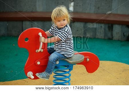 Cute happy baby boy with blond hair in blue tshirt and jeans riding red spring rider or rocker on sunny summer day on playground background