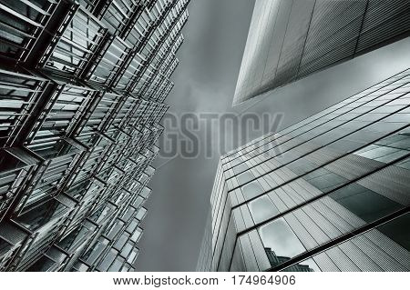 An abstract HDR coloured photo looking up capturing three different buildings on a horizontal degree angle with an applied HDR filter. Image has an added light green tint colour and extra contrast on the sky.
