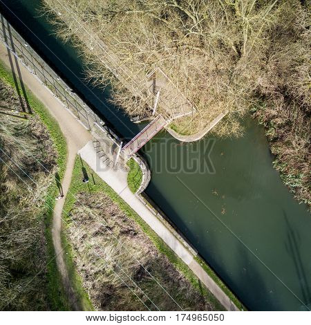 Vertical drone view of an English canal scene with lock and towpath in view surrounded by winter trees on a bright February day.