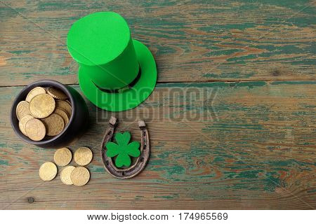 Happy St Patricks Day leprechaun hat with gold coins and lucky charms on vintage style green wood background