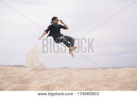 energetic young man jumping high isolated on the sand