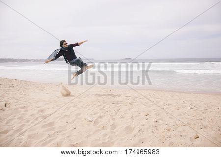 Man jumping high on the sand with freedom isolated on the beach