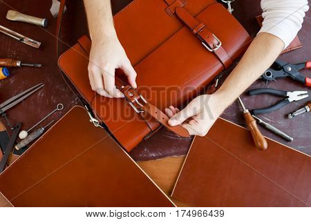 Tanner fastening one of buckles of new leather briefcase