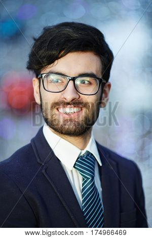 Head and shoulders portrait of young confident Middle-Eastern businessman wearing glasses and elegant suit smiling confidently against blurred office background
