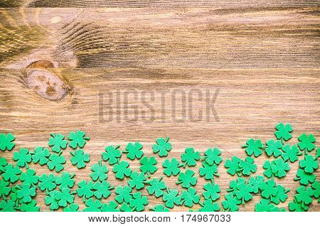 St Patricks Day background with green quatrefoils on the wooden surface. St Patricks Day background with free space for text. Concept of St Patricks Day holiday. St Patricks Day is national Irish holiday