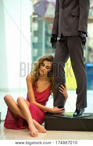 Pretty girl or beautiful woman with long curly hair wearing pink polka dot dress barefoot sits on floor at fashionable male mannequin in suit on shop interior background