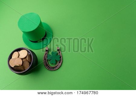 Happy St Patricks Day leprechaun hat with gold coins and lucky charms on green background
