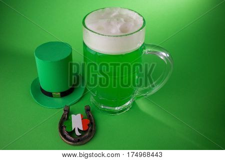 St Patrick's Day green beer with shamrock, horseshoe and Leprechaun hat on green background.