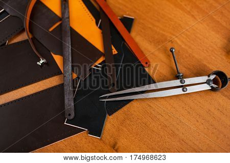Pieces of leather and hand-tools on wooden table