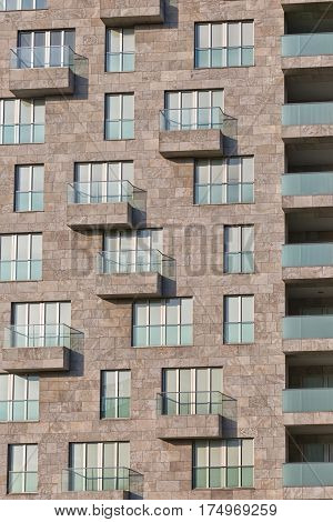 High-end stone facade of an apartment building Glass balconies putting shadow lines on modern facade
