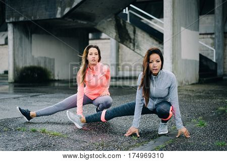 Two Urban Fitness Women Stretching Legs Outside