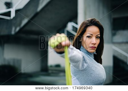 Strong Woman Doing Shoulder Raises Exercise With Resistance Band