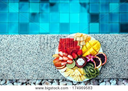 Served fruit plate by hotel pool. Exotic summer diet. Tropical beach lifestyle.