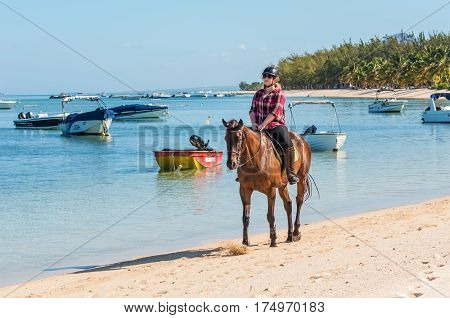 Le Morne Mauritius - December 11 2015: Woman ride horse on the Le Morne Beach one of the finest beaches in Mauritius and the site of many tourism facilities.