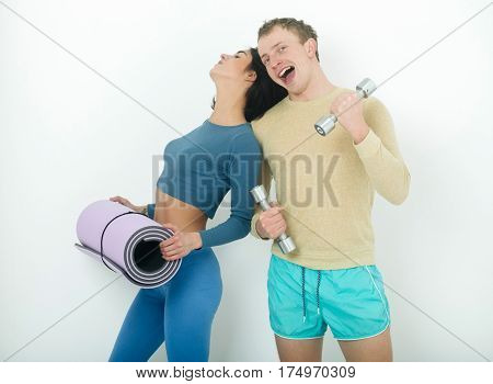 Muscular Man And Girl At Gym With Dumbbells And Mat