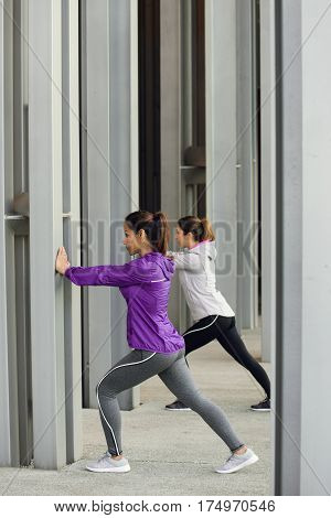 Two Urban Fitness Women Stretching And Exercising