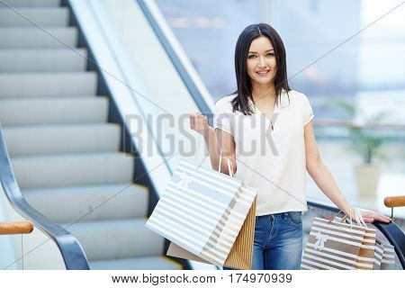 Shopper in casualwear standing by escalator