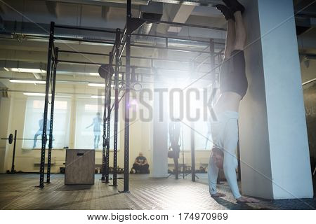 Gymnast doing handstand by wall