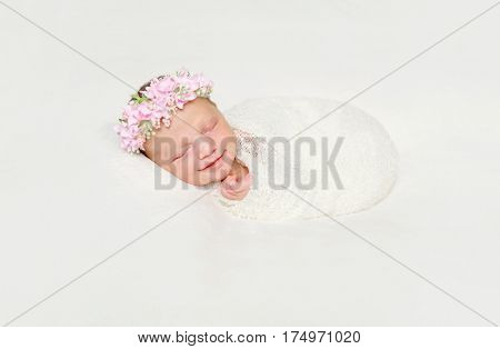 cute newborn baby swaddled in white diaper smiling asleep with flowers on headband