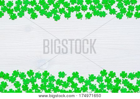 St Patrick Day background - borders of green quatrefoils on the white wooden surface. St Patrick Day white background. St Patricks Day concept background with free space for text.