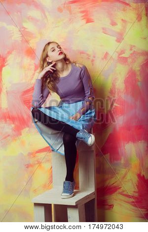 Pretty girl or beautiful woman with red lips and blond curly hair in stylish blue skirt and sneakers sits on wooden chair on pink and yellow wall on abstract background