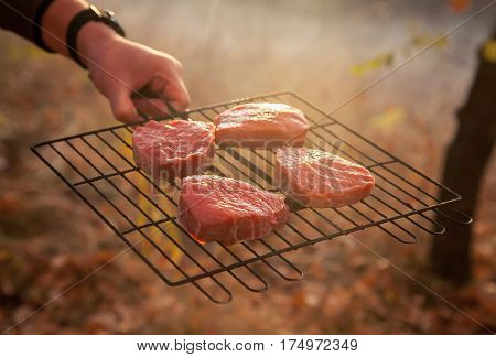 Raw juicy pieces of meat beef, pork, lamb on the grill in the hands of men. Cooking bbq grilling meat on the nature in the forest or park. Spring warm day, the light at sunset.