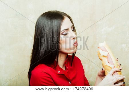 sexy cute woman or pretty girl with brunette long hair and makeup on face in fashionable red shirt holds eats big burger or sandwich with sausage and cheese on textured wall background