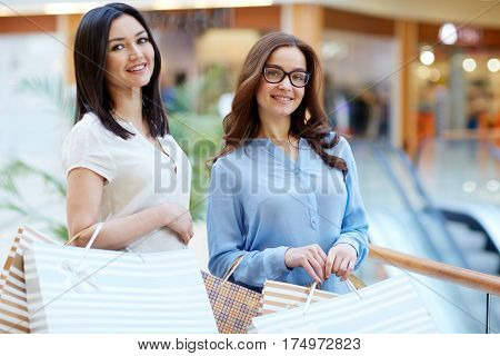 Two young consumers with paperbags shopping in the mall