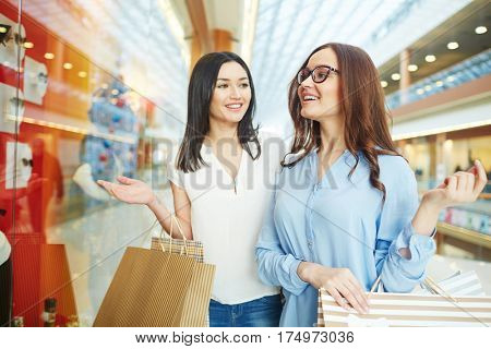 Two young shoppers looking for new clothes in boutique