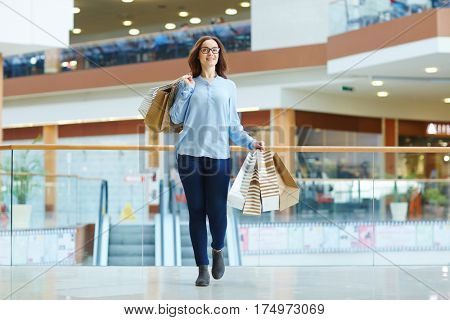 Girl with paperbags walking in the mall