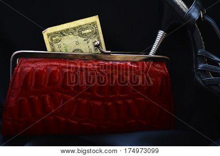 dollar bill peeking out of a red women's wallet under the heel