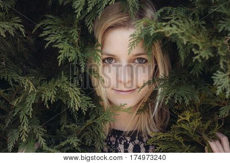 Attractive young woman portrait. Close up portrait in green leaves. Natural beauty young adult woman.