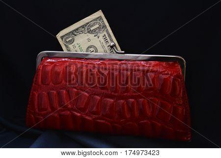 dollar bill peeking out of a red women's wallet