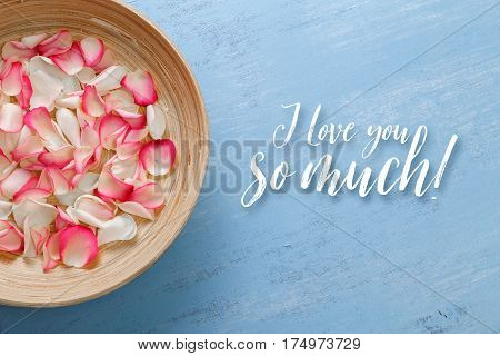 Petals of white and pink roses on blue painted rustic background. Fresh natural flowers in bowl. I love you so much.