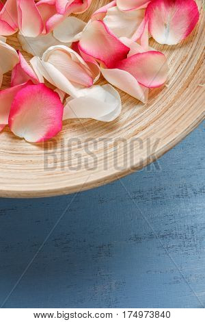 Petals of white and pink roses on blue painted rustic background. Fresh natural flowers in bowl. Dirty grunge wooden board.