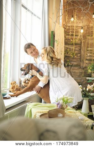husband, pregnant wife and a dog looking into, big window
