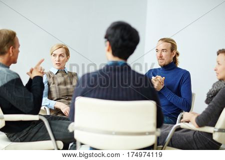 Portrait of mature professional psychologist giving counselling to mental health patients, listening to their problems in support group
