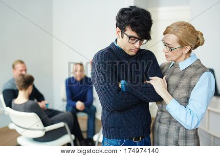 Portrait of mature female psychologist helping young man to overcome his fears and join  group therapy session
