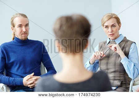 Portrait of mature woman talking to patient in group therapy meeting, consulting about mental health issues