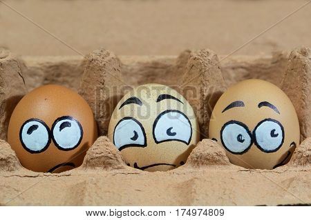 Three frightened egg faces in the brown panel