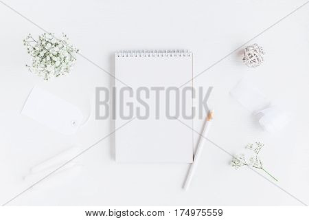Workspace with notebook paper blank gypsophila flowers pencils. Wedding concept. Flat lay top view