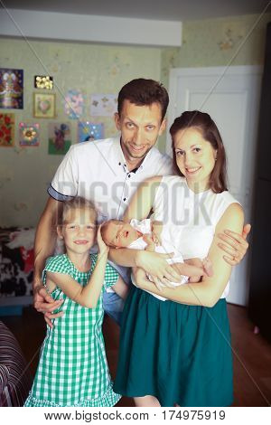 daddy, daughter and mom with a newborn baby in the room for children
