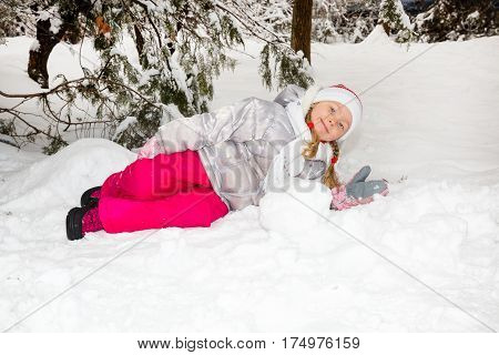Portrait of adorable happy little girl grinning happily at the camera on a sunny winter's day