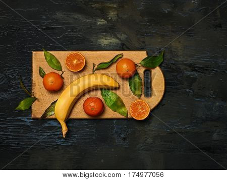 The group of fresh banan and mandarins on a wooden cutting board