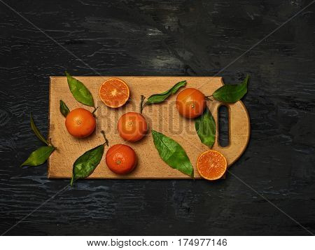 The group of fresh mandarins on a wooden cutting board