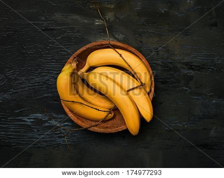 The group of fresh bananas on on a wooden plate